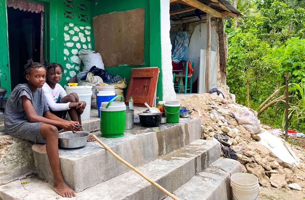Sandra et Samantha assises devant leur maison détruite par le tremblement de terre à Haïti