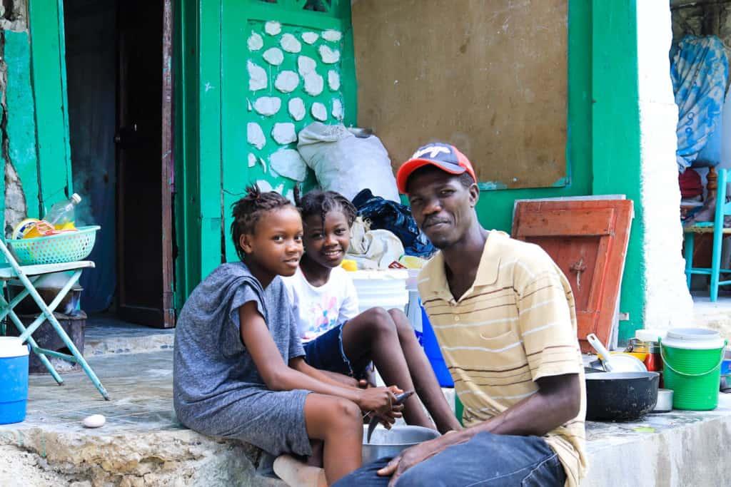 Sandra et Samantha et leur papa devant leur maison détruite par le tremblement de terre à Haïti